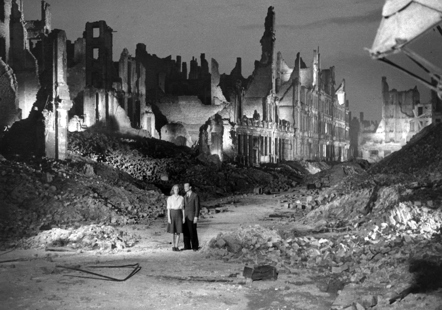 A man and woman are dwarfed by the city rubble surrounding them.
